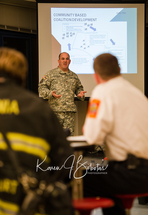 Staff Sgt. Rick Frost of the NH National Guard counterdrug task force addresses the group on developing a community based coalition against the rising drug abuse in the city at Laconia Middle School Thursday evening.  (Karen Bobotas/for the Laconia Daily Sun)