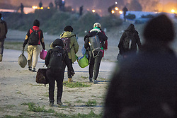 """© Licensed to London News Pictures . 23/10/2016 . Calais , France . People carrying bags and luggage at the Calais migrant camp known as """" The Jungle """" , in Northern France , on the evening before the start of the eviction and destruction of the camp . Photo credit: Joel Goodman/LNP"""