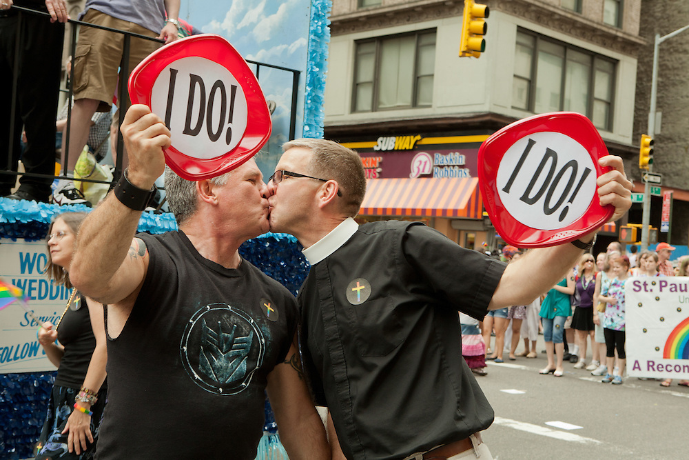 """A male couple, one in a clerical collar, exchange a kiss while marching with St. Peter's Church, bearing signs lettered """"I Do"""" in the 2011 Pride Parade on New York's Fifth Avenue."""