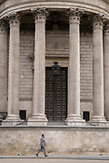 A man walks beneath the pillars and column architecture of Sir Christopher Wrens St Pauls Cathedral south transept, on 24th June 2021, in London, England.