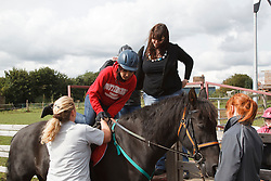 Man with visual impairment having riding lesson, getting on horse.