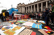 Protesters lay out signs in front of Parliament House. Protesters have been marching peacefully through the city in groups of 100 as part of an Invasion Day rally. The Australia Day protest went ahead despite coronavirus rules limiting gatherings to 100 people. (Photo by Michael Currie/Speed Media)