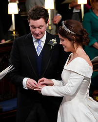 Princess Eugenie smiles as Jack Brooksbank put the ring on her finger during their wedding ceremony at St George's Chapel in Windsor Castle.