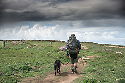 A man and his dog walk along the South West Coastal path at Carnews at Bederuthan in Cornwall.