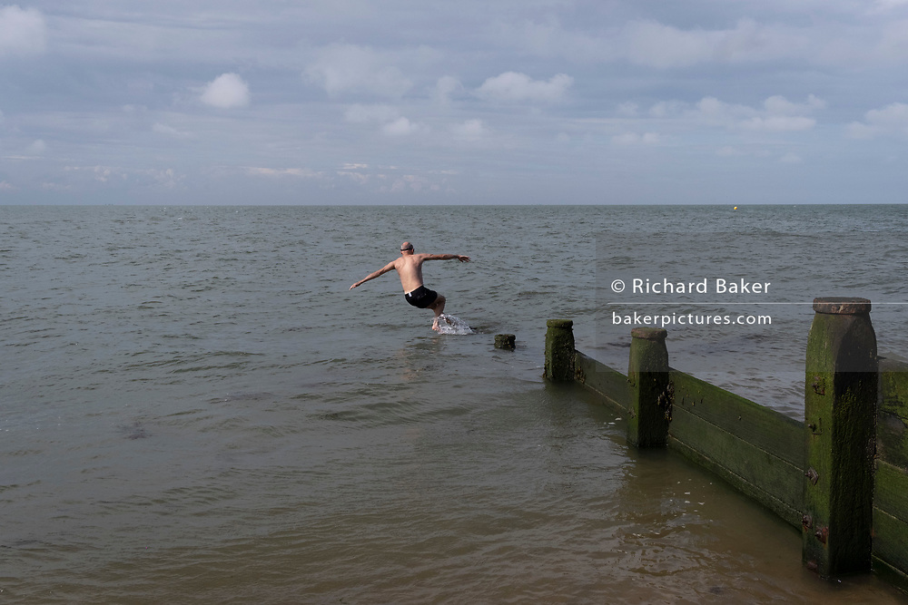 A wild swimmer dives off a beach sea defence groyne into the cold tidal waters of the Thames Estuary, on 25th July 2021, in Whitstable, England.