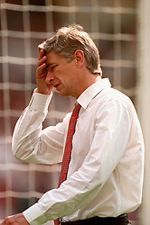 Arsenal manager Arsene Wenger walks out at Wembley for the second half with a headache