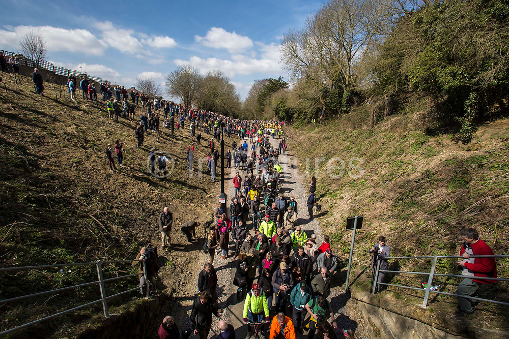 A landscape view of a large group of of enthusiastic people gather at the entrance and embankment of the Devonshire Tunnel for the official opening of the Bath Two Tunnels Greenway on 6th April 2013.  The 13 mile shared-path is a dramatic and accessible route leading south from Bath city and is accessible by foot, cycle, buggy and wheelchair. This development was started by a local community group and is part of the Sustrans lottery-funded project, Connect 2 Cycling Network. Sustrans is a charity that works with communities, policy-makers and partner organisations so that people can choose healthier, cleaner and cheaper journeys and enjoy better, safer spaces to live in. The event was attended by hundreds of cyclists and pedestrians of all ages and abilities. Bath, Somerset, United Kingdom.
