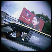 A taxi driver drives past a billboard bearing an image of a Bollywood actress in Kabul.