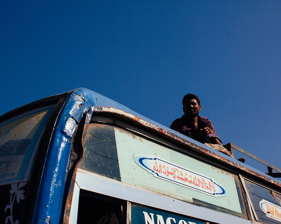 Man travelling on the roof of a bus in Bangladesh