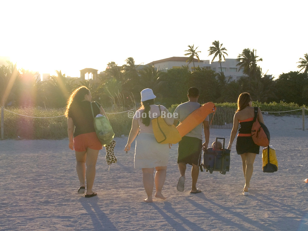 group of people walking home after a day on the beach