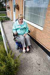 Woman wheelchair using the ramp outside her house,