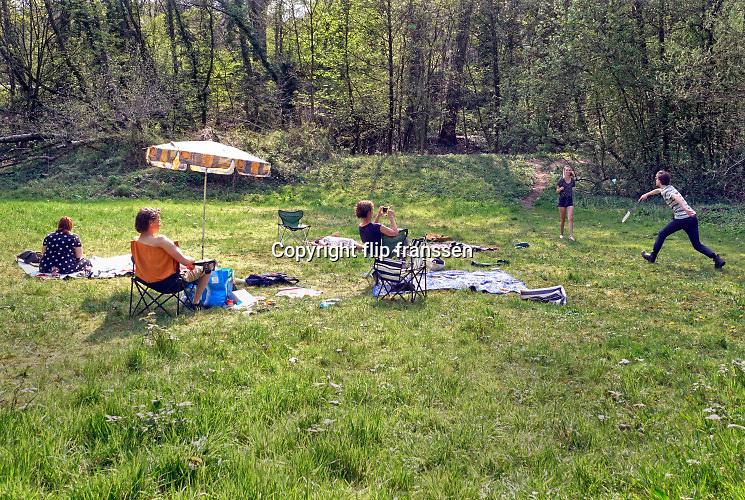 Nederland, Ubbergen, 12-4-2020  Bewoners van woongemeenschap de Refter zitten buiten in het gras. Twee mensen zijn aan het sporten, badminton .vanwege de coronadreiging houden zij gepaste anderhalve meter afstand.Foto: Flip Franssen