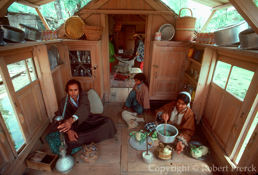 INDIA, KASHMIR a family cooking in the kitchen of their  home, a traditional wooden houseboat on a canal in Srinager, the capital of Kashmir