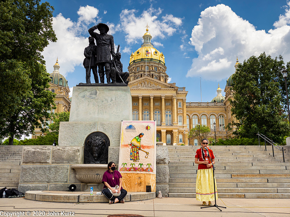 04 JULY 2020 - DES MOINES, IOWA: DONIELLE WANATEE, a member of the Thunder Clan of the Meskwaki Nation, talks about the stereotypical depiction of Native Americans in artwork in Iowa State Capitol. She is speaking in front of the Pioneer Statuary Group, which Native Americans say has a Native American depicted as being subservient to White pioneers. The statue was started in 1890 and finished in 1892. It was one of the first monuments on the grounds of the Capitol. Hundreds of people came to the grounds of the Iowa State Capitol to protest against and in favor of historic monuments on the capitol grounds. Several hundred people protested against a monument to Christopher Columbus and the stereotypical depiction of Native Americans on the capitol grounds. About 50 people came to the capitol to rally in support of the monuments. The protest against the monuments was organized by Seeding Sovereignty, a collective of indigenous women. The rally to defend the monuments was organized by an Iowa chapter of Three Percenters.      PHOTO BY JACK KURTZ