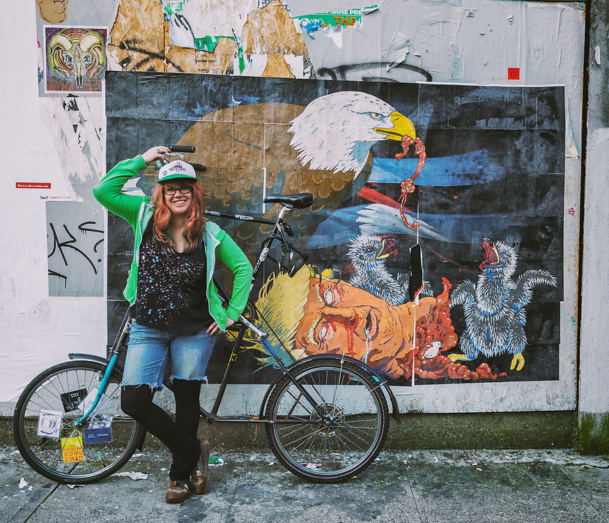 http://obviouslycloe.org/ is an illustrator living and working in Portland, OR, USA. She is an active member of the bike community, an intersectional feminist and has 2 of the best dogs in the world, Dilwyn and Nerys. Here we have her with her tall bike and her work on the wall.