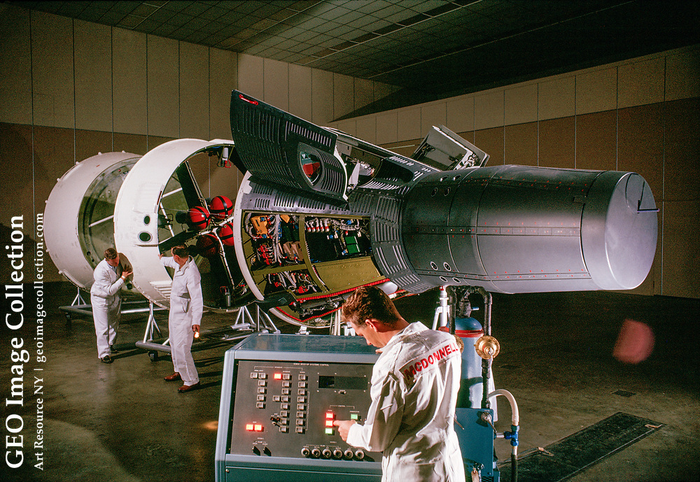 An engineer checks out a console and a Gemini capsule with its service module.