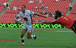 JOHANNESBURG, South Africa, 02 April 2011. Quade Cooper of the Reds gets away from a diving Joshua Strauss of the Lions during the Super15 Rugby match between the Lions and the Reds at Coca-Cola Park in Johannesburg, South Africa on 02 April 2011. .Photographer : Anton de Villiers / SPORTZPICS