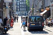 In Amsterdam moet een fietser bijna afstappen als hij in de verdrukking komt met een busje in een smalle straat in de binnenstad.<br /> <br /> In Amsterdam, a cyclist has almost get of his bike as he is compromised by a van in a narrow street in the city.