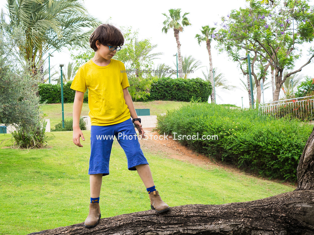 Young boy of ten in yellow t-shirt and blue baggy pants plays alone in a garden. Model release available