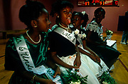 At a beauty talent contest, the finalists line up to await the judges decision. The girls are dressed in all their finery with dresses, pinned up hair and sashes as they're seated in the gym at the Bedford-King Recreation Center in Atlanta, Georgia. The black community hold annual events here including sports competitions and occasions such this pageant where the girls and also boys prove their talents and potential. One young lady however, sees fit to poke her tongue out at the viewer in a cheeky display of humour and character. Her rivals seem oblivious and unaware of her irreverence but perhaps the judge is watching and her chances of winning are now impossible!