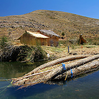 South America, Bolivia, Lake Titicaca. Floating reed island and boat of Lake Titicaca.