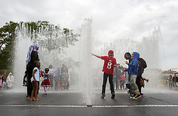 © Licensed to London News Pictures. 26/06/2014. London, UK Despite the cloud people play in the fountains installed in London's South Bank today 26 June 2014, temperatures in the City remain warm. Photo credit : Stephen Simpson/LNP
