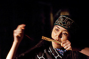 An Ainu woman playing a Mukkuri, a traditional Japanese Ainu percussion instrument, at the Ainu Museum. The Ainu people are indigenous to Japan and Russia. Lake Poroto, Hokkaid?, Japan
