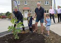 David Beckham (left), Michael Eavis and his grandsons Noah and George plant a tree outside a completed house in a housing development in Pilton village in Somerset.