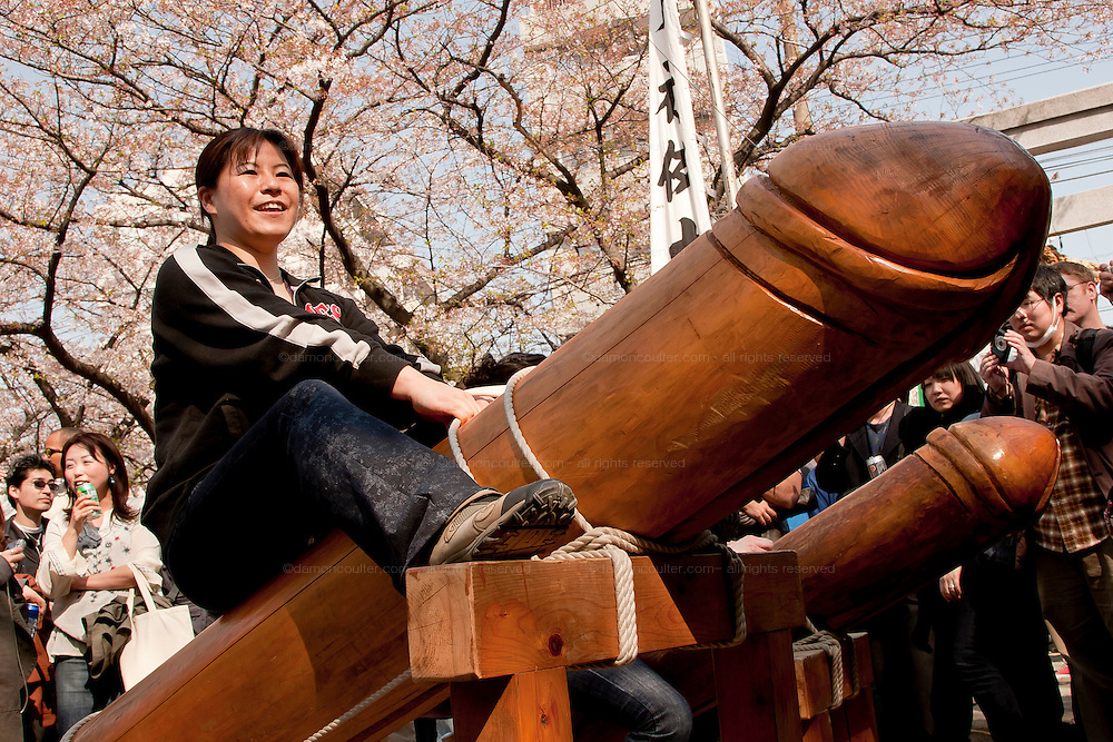Tourist pose on top of large wooden phalluses in the grounds of Wakamiya Hanchiman gu shrine during the Kanamara matsuri or festival of the iron Phallus in Kawasaki Daishi, Kanagawa, Japan April 6th 2008