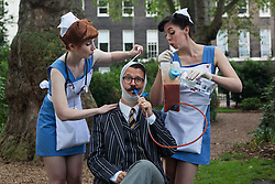 © licensed to London News Pictures. London, UK 08/07/2012. Two vintage nurse lookalikes posing with a man at the Chap Olympiad in Bedford Square Gardens in central London today.the Chap Olympiad describes itself as a celebration of eccentricity and athletic ineptitude with the emphasis on panache and style over sporting prowess. the Chap Olympiad describes itself as a celebration of eccentricity and athletic ineptitude with the emphasis on panache and style over sporting prowess. Photo credit: Tolga Akmen/LNP
