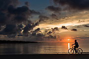 Silhouette of a bicyclist at sunrise on Isle of Palms beach at Wild Dunes near Charleston, South Carolina.