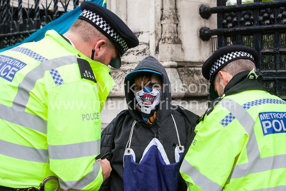 """London, UK. 25 September, 2019. Metropolitan Police officers detain a masked protester outside the Houses of Parliament on the day after the Supreme Court ruled that the Prime Minister's decision to suspend parliament was """"unlawful, void and of no effect""""."""