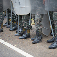 Army with riot police equipment and improvised metal truncheons prepare to confront protestors in Olancho.