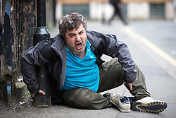 © Licensed to London News Pictures . 06/04/2017 . Manchester , UK . A man appears disorientated and screams out incoherently as he sits forward on the pavement on Newton Street . An epidemic of abuse of the drug spice by some of Manchester's homeless population , in plain sight , is causing users to experience psychosis and a zombie-like state and is daily being witnessed in the Piccadilly Gardens area of Manchester , drawing large resource from paramedic services in the city centre . Photo credit : Joel Goodman/LNP