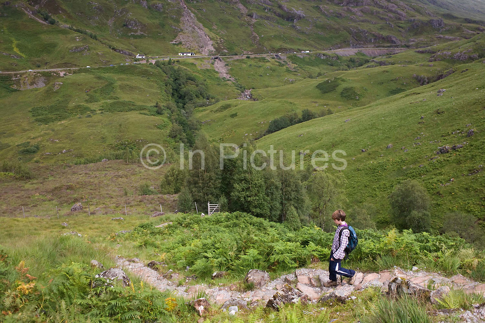 A young walker descends Glencoe's Lost Valley (in Gaelic: Coire Gabhail). Carefully making his way down solid stone steps prepared especially for inexperienced trekkers, the lad descends down towards a deer fence to continue into a small copse. The A82 road is seen way below, a route through Glencoe serving locals and many thousands of tourists who come to this region of northern Britain for its dramatic landscape, if unpredictable weather. Wearing a small daypack, the boy is ahead of his family, eager to explore more of this countryside on his own. He is a free-spirit, enjoying his boyhood and increasing independence.