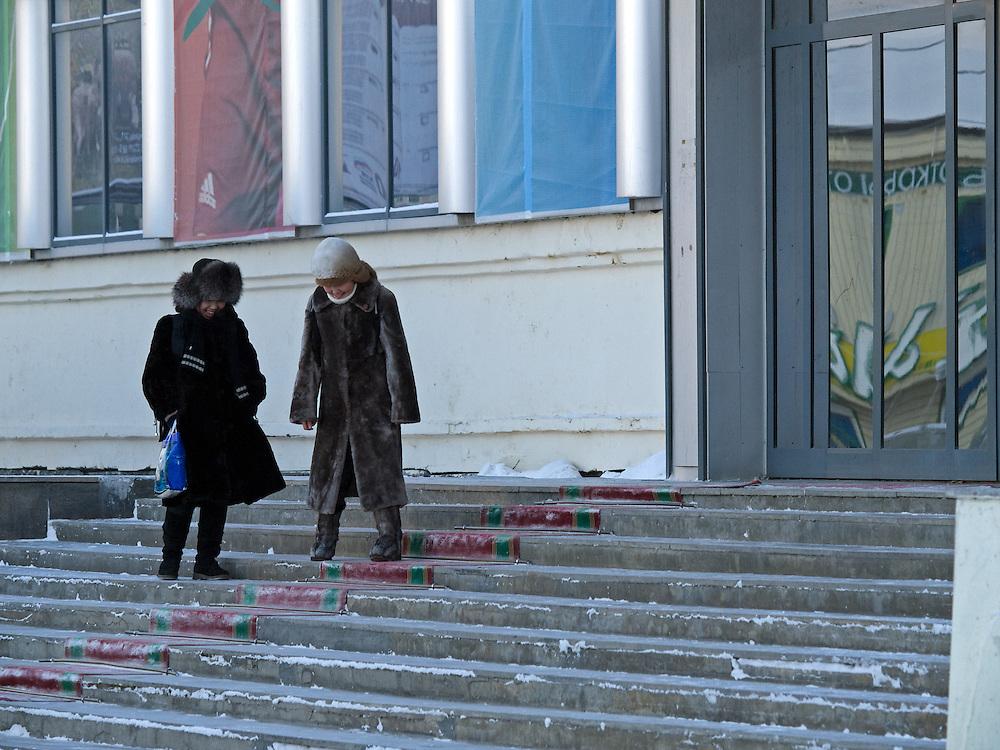 Passanten in der Innenstadt von Jakutsk. Jakutsk wurde 1632 gegruendet und feierte 2007 sein 375 jaehriges Bestehen. Jakutsk ist im Winter eine der kaeltesten Grossstaedte weltweit mit durchschnittlichen Winter Temperaturen von -40.9 Grad Celsius. Die Stadt ist nicht weit entfernt von Oimjakon, dem Kaeltepol der bewohnten Gebiete der Erde.<br /> <br /> Passersby in the city center of Yakutsk. Yakutsk was founded in 1632 and celebrated 2007 the 375th anniversary - billboard announcing the celebration. Yakutsk is a city in the Russian Far East, located about 4 degrees (450 km) below the Arctic Circle. It is the capital of the Sakha (Yakutia) Republic (formerly the Yakut Autonomous Soviet Socialist Republic), Russia and a major port on the Lena River. Yakutsk is one of the coldest cities on earth, with winter temperatures averaging -40.9 degrees Celsius.