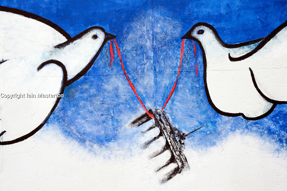 Painting of two doves holding Brandenburg Gate on Berlin Wall repainted in May 2009