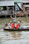 5 youth in a boat waving. On the Mekong River, Cai Be, Tien Giang Province, Vietnam