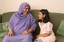 Grandmother and grandchild chatting on the sofa,