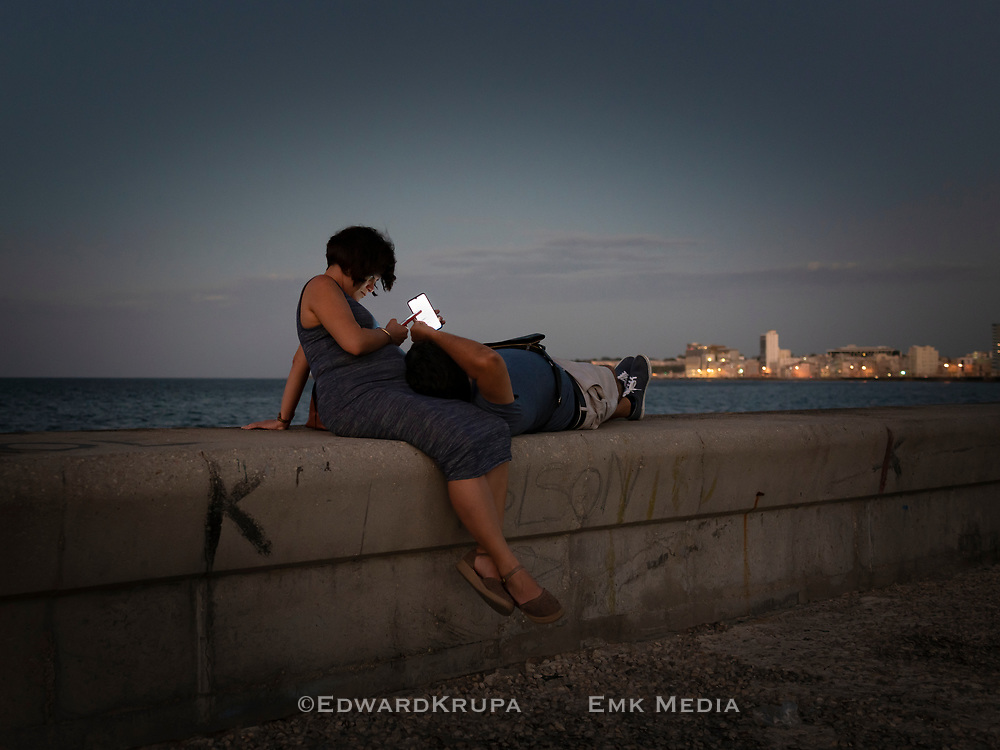 A couple shares a moment together on their devices at the Malecon/Sea wall in Havana, Cuba on Valentines Day.