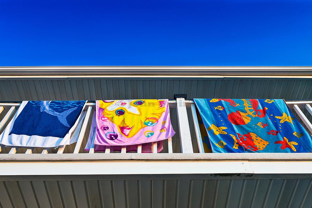 Beach towels dry on hotel balcony.
