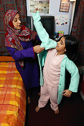 Single parent helping her young daughter get ready for bed,