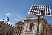Beneath Romanesque architecture of the Palais de Justice is modern solar panel technology on 17th June 2016, in Montpellier, France. Looking up at the heritage buildings of this provincial French town, with their pillars and columns from another era, along with ornate street lighting.