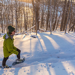 A woman snowshoeing while the sun shines through the forest above Indian Hill Reservoir in West Newbury, Massachusetts.