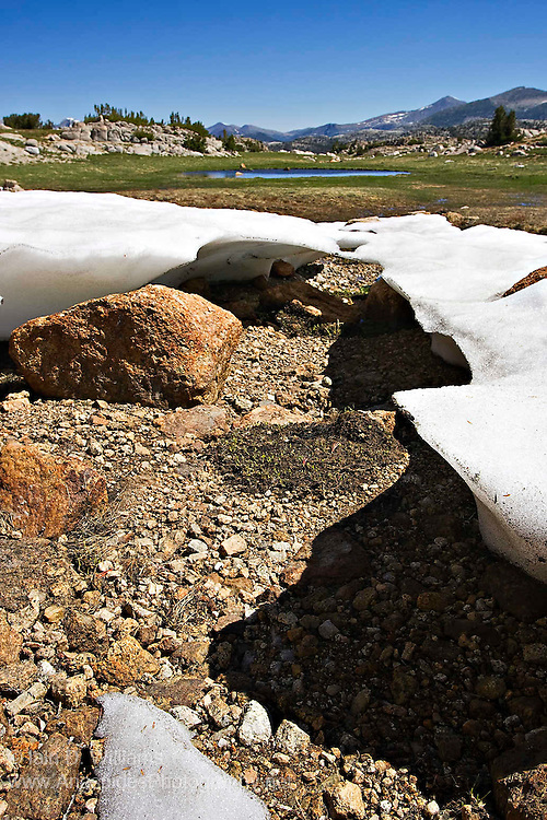 The remains of an extensive snow and ice field in the High Sierras in Yosemite National Park.  Summer temperatures have all but melted the field leaving small areas of ice that have been eroded beneath by flowing water