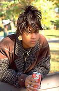 African American female age 15 thoughtfully leaning on bridge.  St Paul Minnesota USA