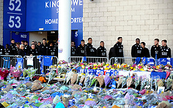 Leicester City players look at tributes outside Leicester City Football Club after a helicopter crashed Saturday killing Leicester City's owner, Thai billionaire Vichai Srivaddhanaprabha and four other people, in Leicester, England, Monday Oct. 29 2018. The helicopter crashed in flames in a car park next to the soccer club's stadium shortly after it took off from the pitch following a Premier League game on Saturday night. (AP Photo/Rui Vieira)