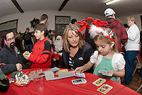 Jacob, Samuel, Becky and Molly Reposa look through their gifts from Santa at the Wicwas Grange Saturday evening along with dozens of friends and families during their annual Christmas party celebration.  (Karen Bobotas/for the Laconia Daily Sun)