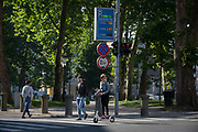 A woman wearing pink slippers rides her scooter across a junction on Slovenska Cesta street in the Slovenian capital, Ljubljana, on 25th June 2018, in Ljubljana, Slovenia.