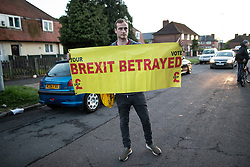 © Licensed to London News Pictures . 25/04/2019. Manchester, UK. A man holds up a BREXIT BETRAYED banner on the street by the event . Stephen Yaxley-Lennon (aka Tommy Robinson ) announces he is running for a seat in the European Parliament in North West England at a barbecue event on a green on a housing estate in Wythenshawe , South Manchester . Photo credit: Joel Goodman/LNP